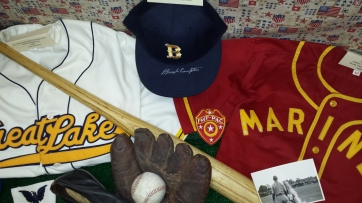 "The mitt is a U.S. Navy stamped glove from WWII. The ball cap is a 1980s vintage UCLA team cap that was signed by Bruins HoF catcher, LT. Lynn ""Buck"" Compton (Co. E, 506th PIR, 101st A/B)."