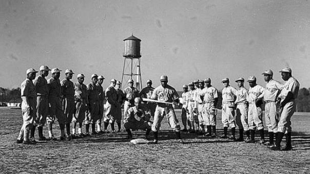 The service teams, though segregated (like the wartime U.S.armed forces) also featured African-American teams and the Marines were no different. This team from Montford Point (at Camp Lejune, NC) featured a star of the Negro Leagues (Dan Bankhead) who would go on to be the first pitcher in the major leagues, playing for the Brooklyn Dodgers. Note the two squads of players – those on the left are wearing the road gray and the players on the right are in white.