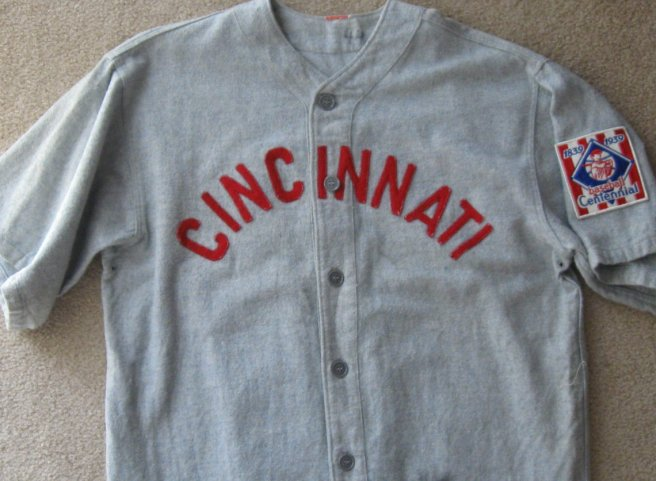 This replica 1939 Cincinnati Reds uniform (an accurate reproduction used in the 1984 film, The Natural) shows the red felt block lettering and the curve of the arch that forms the word. Note the absence of any sort of piping (source: BidAMI.com).