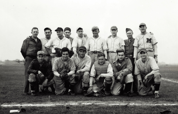"United States Army Air Force ballplayers. There is a hodgepodge of uniforms on display in this image. In addition to the Cincinnati and ""M"" jerseys, the player in the front row (2nd from right) is wearing a uniform with thin, double-piping). The player in the bomber jacket (front row, far left) is wearing a 6 panel hat with piping outlining each panel."