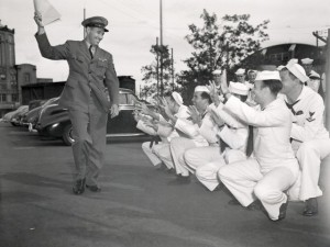 23 Aug 1945, Chicago, Illinois, USA --- 8/23/1945-Chicago, IL: With papers placing him on the Navy's inactive list in hand, Chief Specialist Bob Feller, Cleveland Indian pitcher, finds plenty of volunteer catchers in case he decides to practice his pitching arm and toss away precious papers. Feller waves goodbye as he leaves the Navy Demobilization Center at Navy Pier. --- Image by © Bettmann/CORBIS