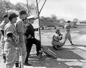 """Harold """"Pee Wee"""" Reese takes a swing at the plate for the Norfolk Training Station's Blue Jackets team. (Former) New York Yankees' shortstop Phil Rizzuto (nearest at left) watches with his Bluejackets teammates."""