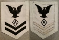 "Specialist ""A"" 2/c rating badge for dress whites. Both chevrons are sewn onto the backing material while the ""crow"" and insignia are directly embroidered which dates this rating badge to World War II."